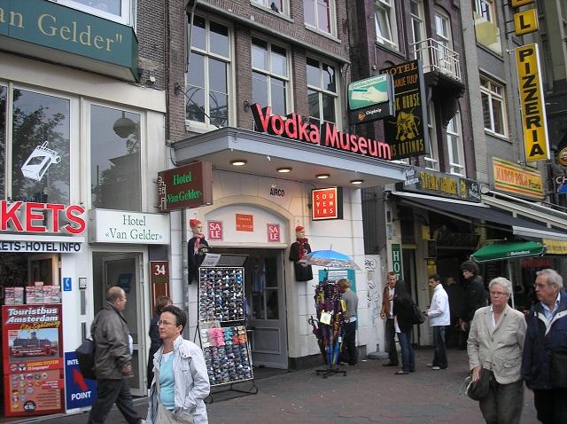 Der Damrak mit Souvenirgeschäften und Vodka Museum in Amsterdam